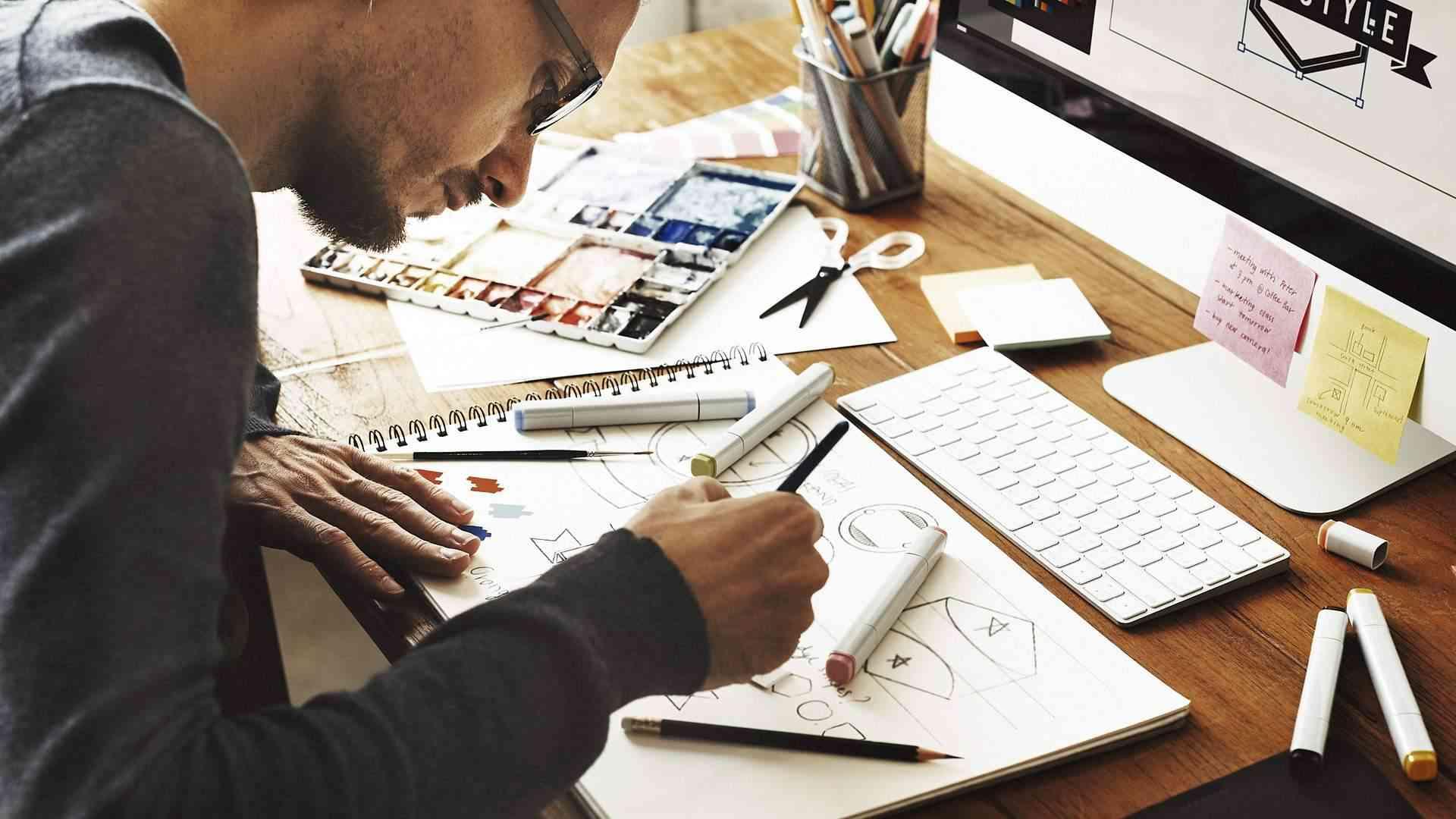 Designer fazendo projeto no papel, com computador mais à frente