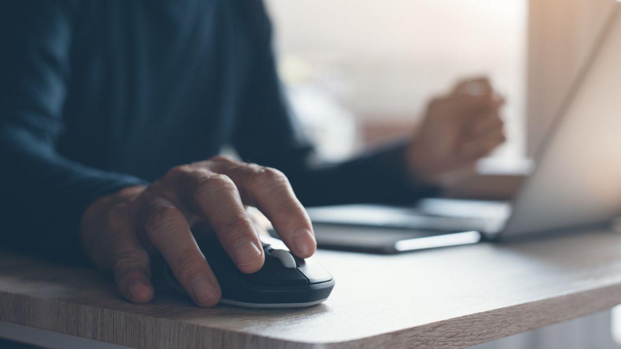 Homem usando mouse sem fio em uma mesa com um notebook