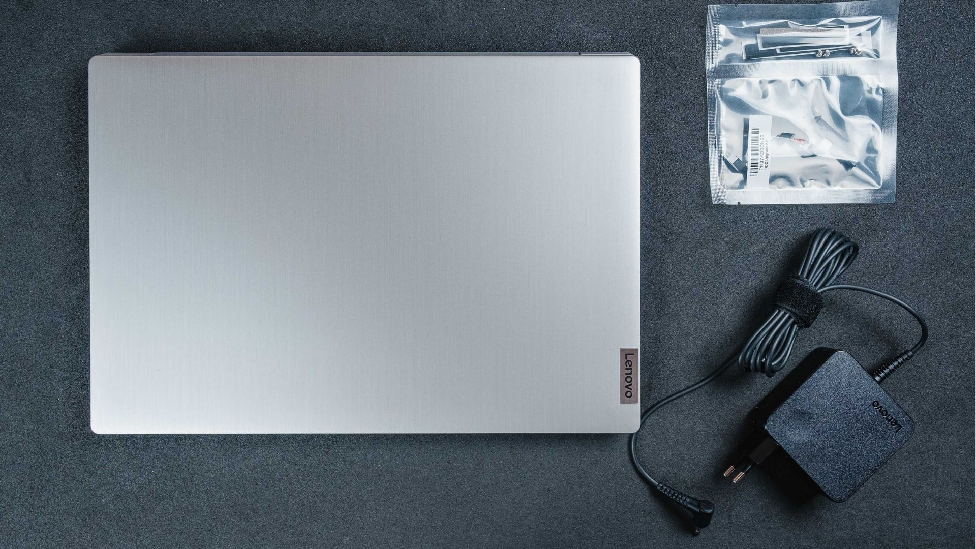 Lenovo IdeaPad 3i visto de cima ao lado de carregador e kit para upgrade