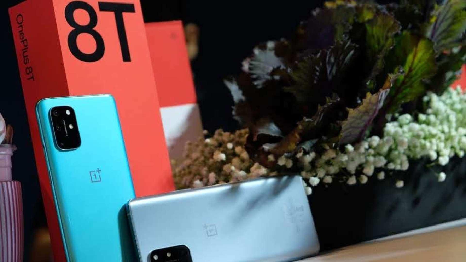 Dois celulares One Plus 8T apoiados em suas caixas ao lado de vaso de plantas