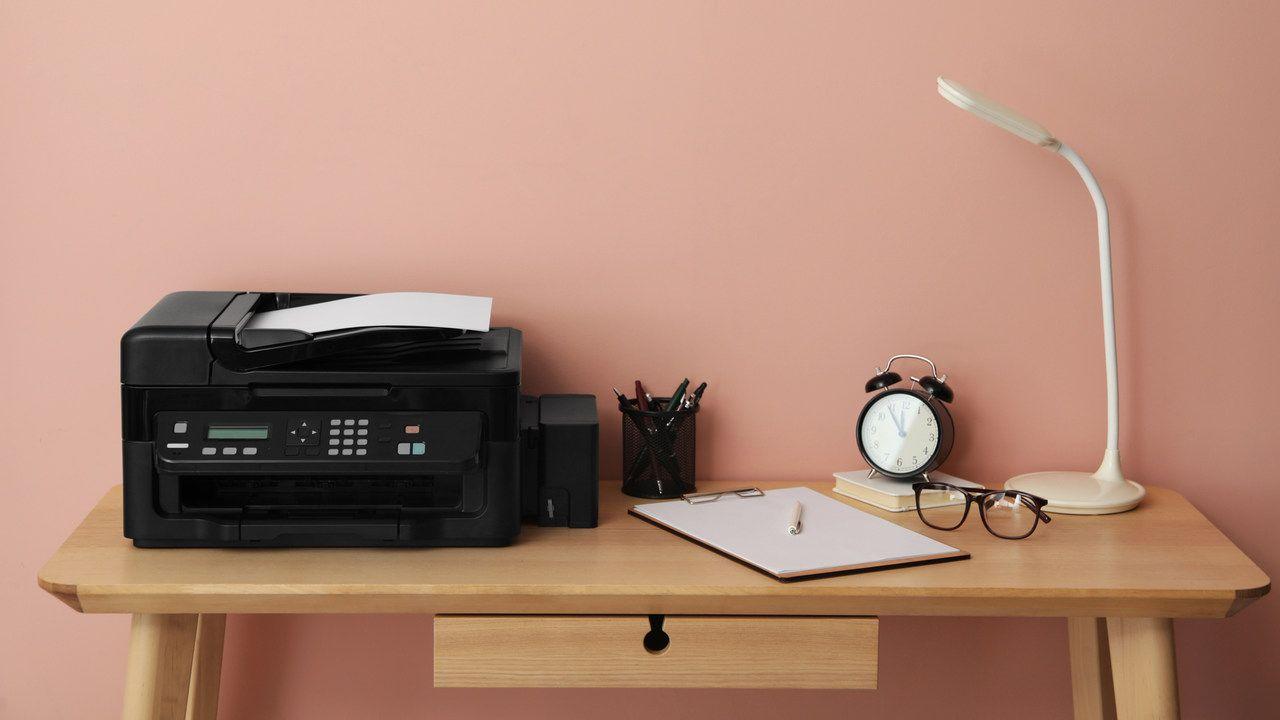 Preço de uma impressora preta, com dispositivo sobre uma mesa