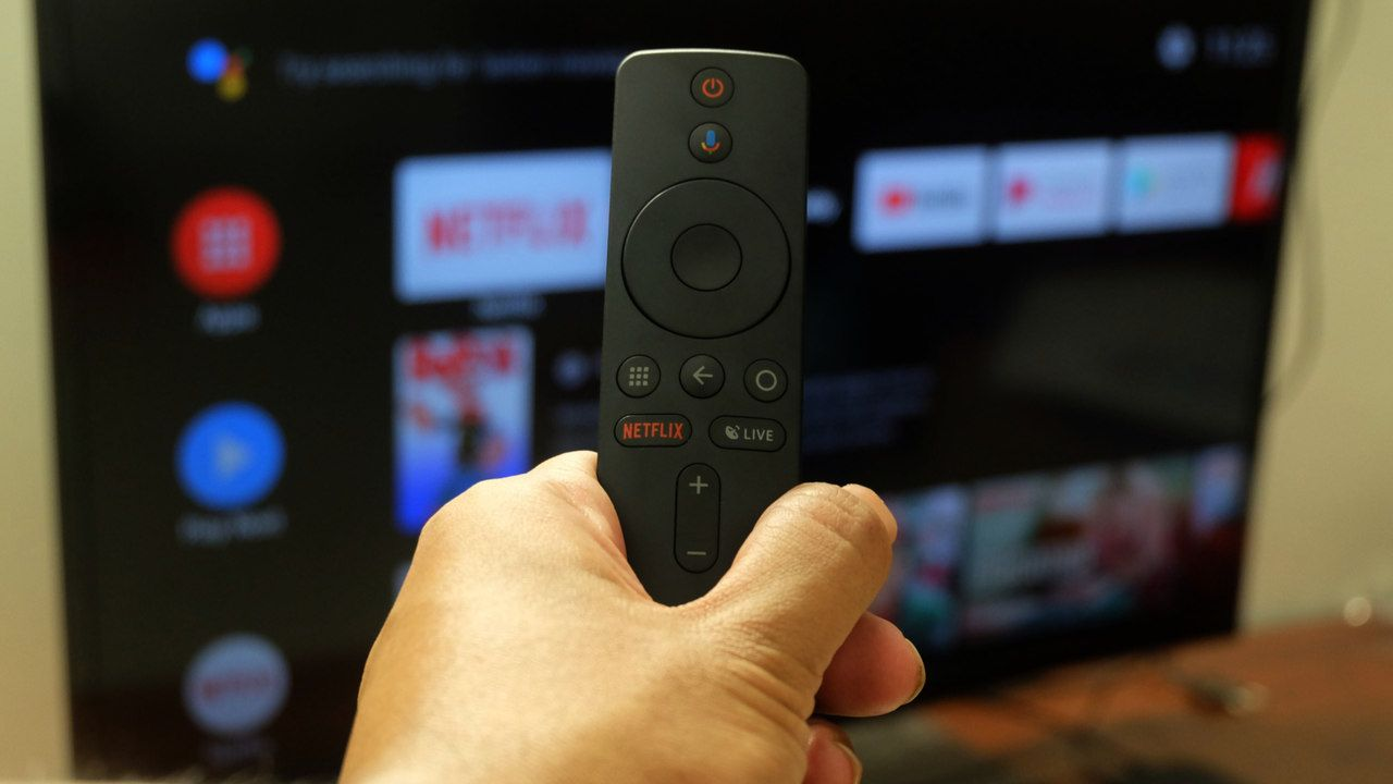 Controle remoto de uma TV box com tela de uma televisão aberta no menu de aplicativos ao fundo