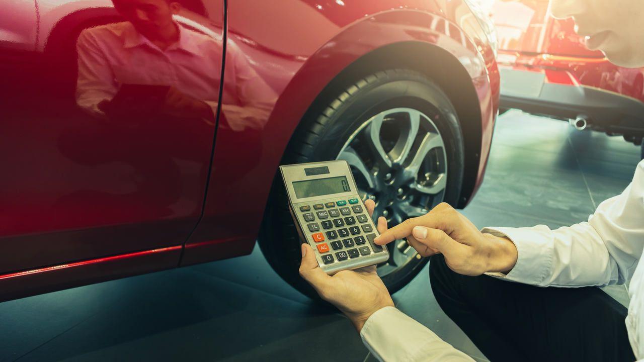 Homem segurando calculadora em frente a um pneu de um carro vermelho