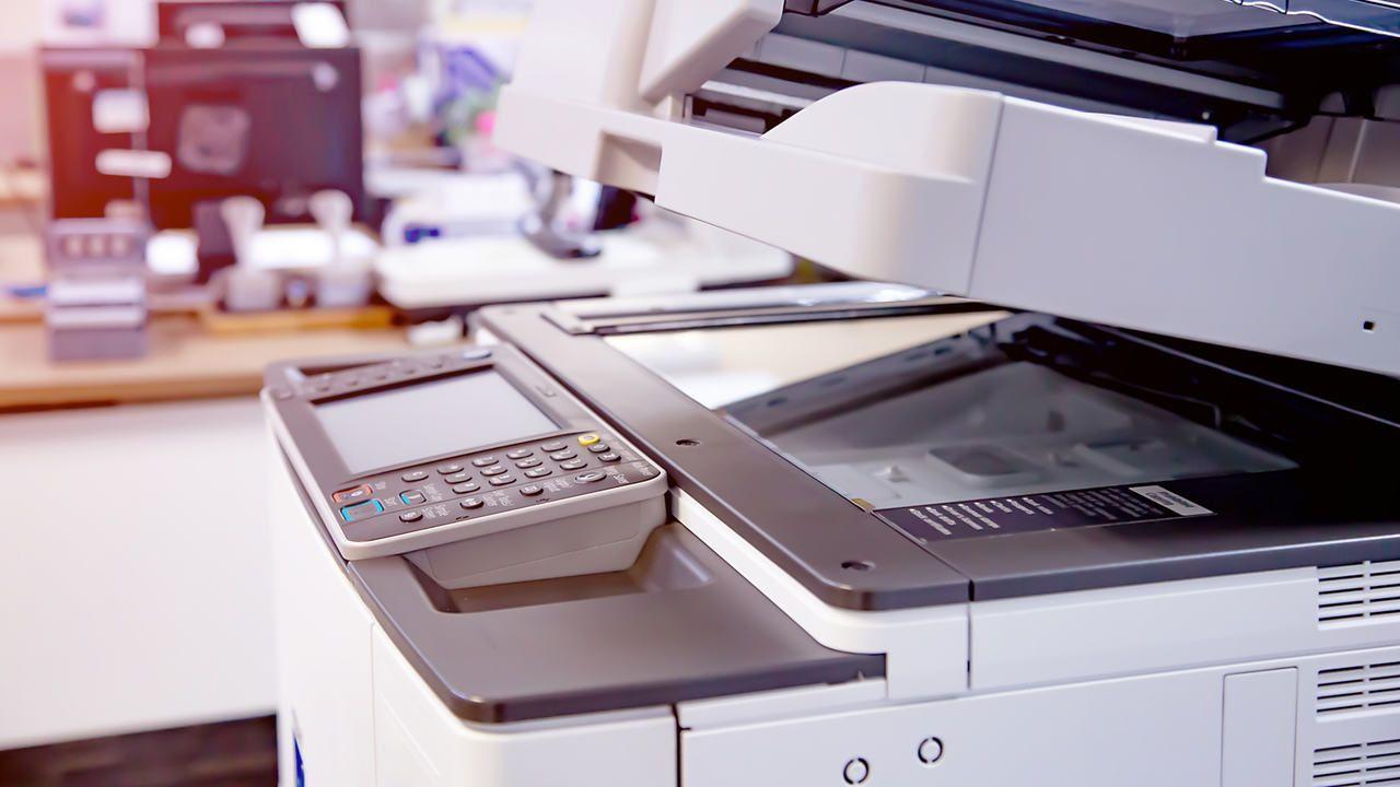 Impressora branca com vidro do scanner semi aberto em escritório