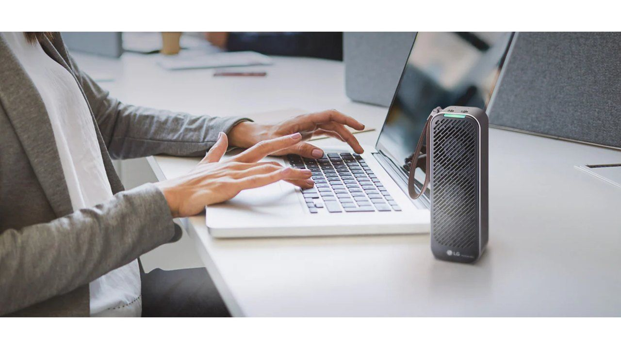 Purificador LG PuriCare Mini sobre bancada branca enquanto uma mulher trabalha ao lado no notebook
