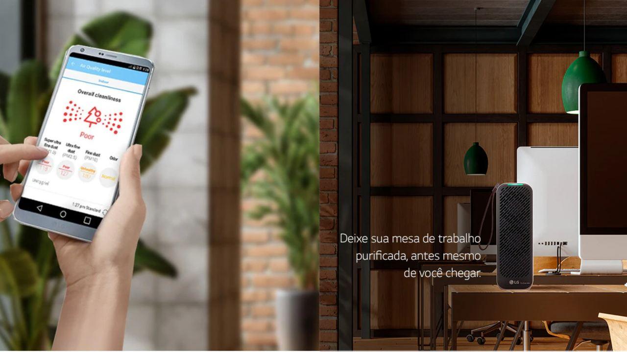 Purificador LG PureCare cinza apoiado em mesa de madeira, enquanto mãos seguram um celular com o aplicativo do purificador aberto na tela