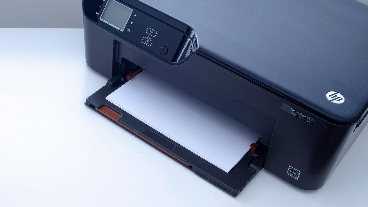Impressora HP preta com papel saindo pela bandeja de impressão