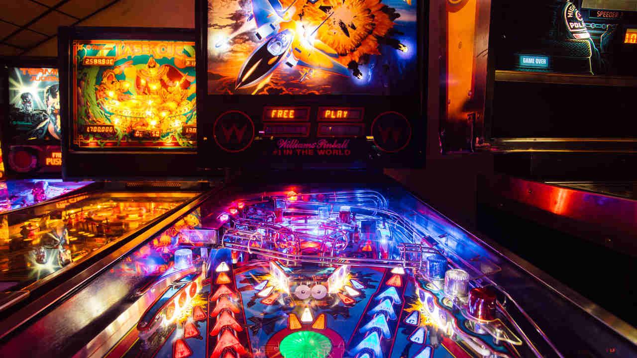 Máquina de pinball cheio de luzes em um arcade com outras máquinas de jogos