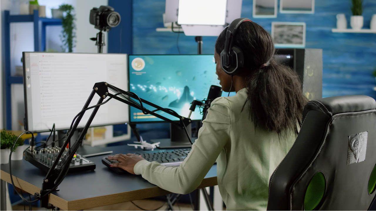 Mulher falando em frente ao microfone gamer enquanto olha para o computador