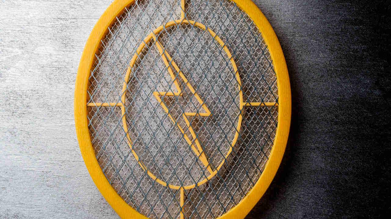 Raquete elétrica com aro amarelo e raio também amarelo no centro da trama apoiada sobre superfície cinza
