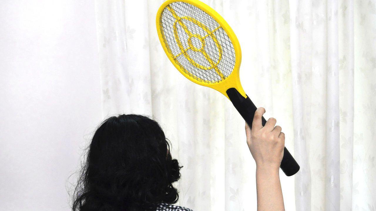 Mulher de costas segurando raquete elétrica amarela com cabo preto