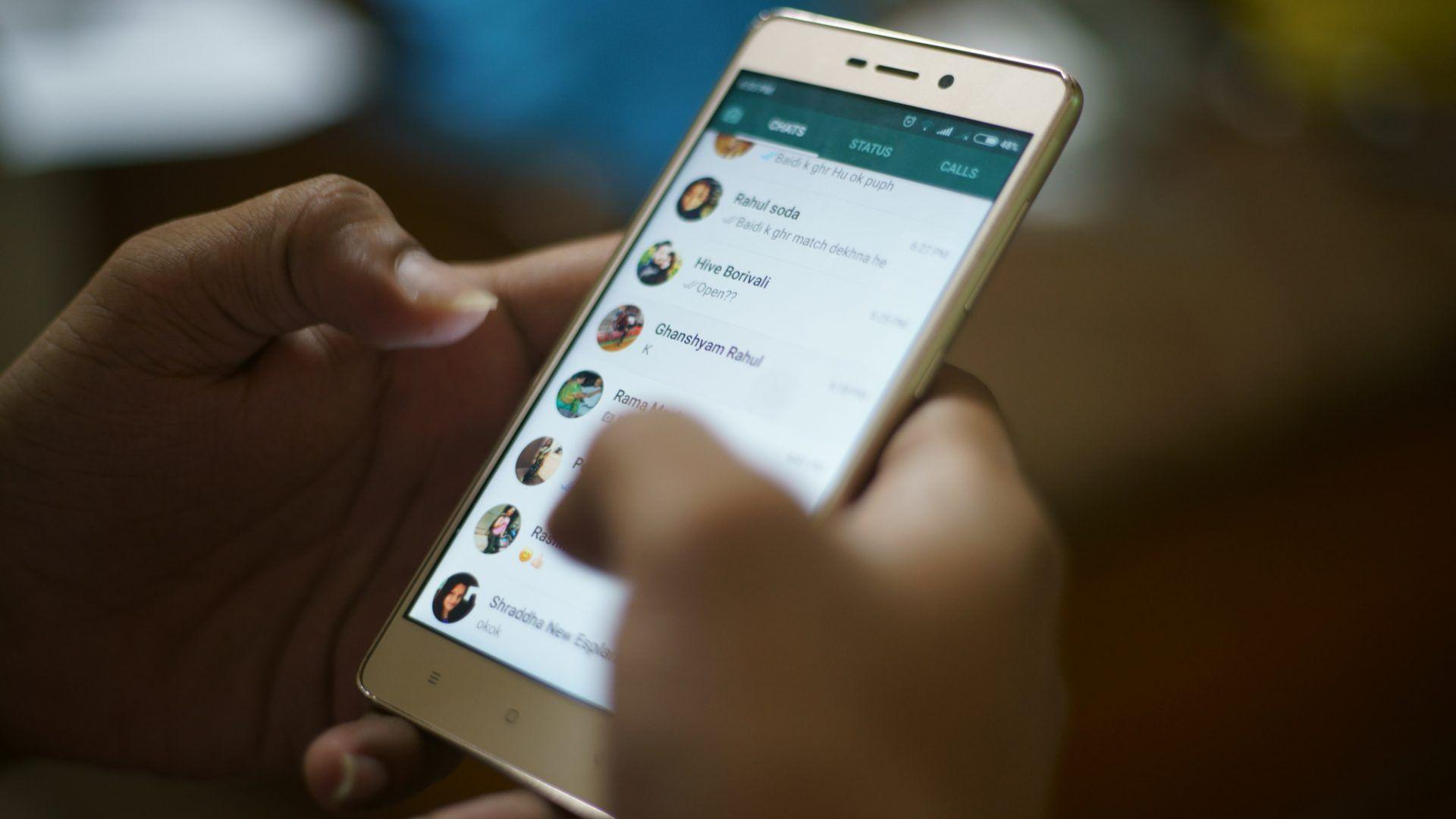 Imagem de duas mãos usando o WhatsApp em um celular