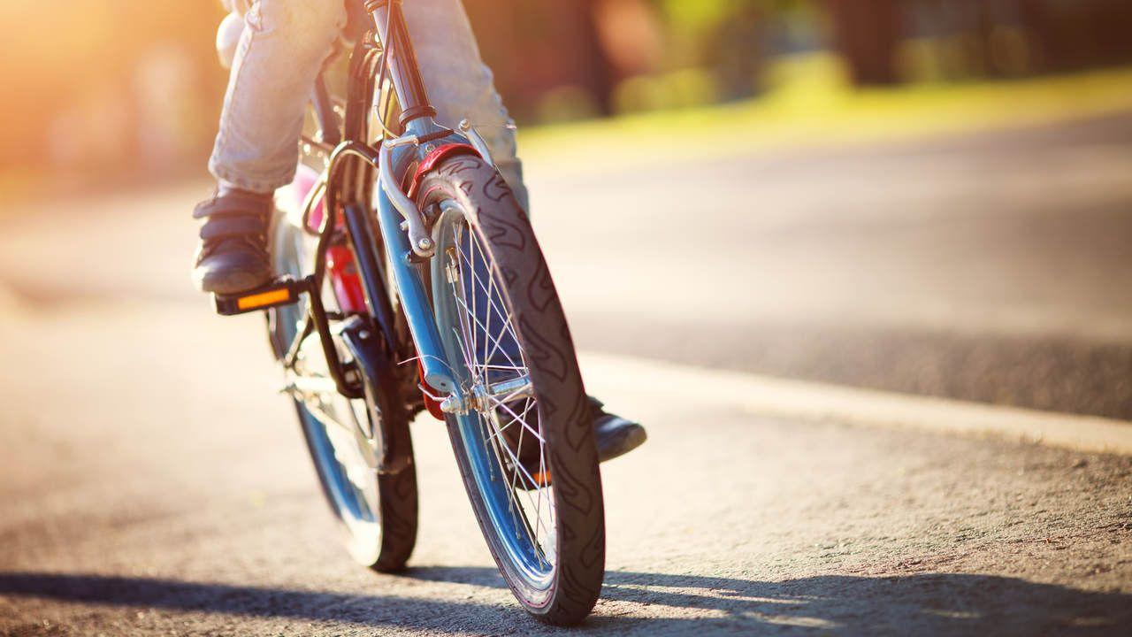 Garoto pedalando ao ar livre em bicicleta vermelha