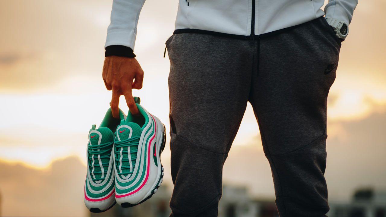 Homem segurando um tênis Nike Air Max em tons de verde, rosa e branco