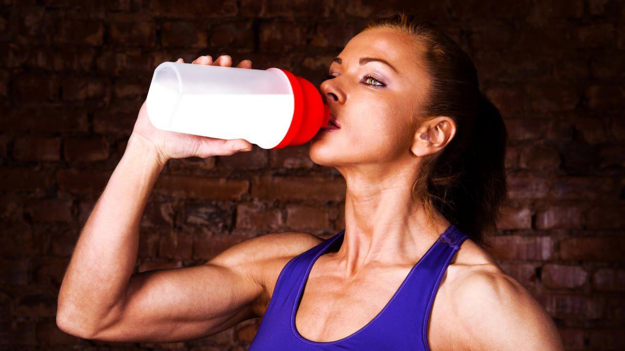 Mulher bebendo shake pós treino em coqueteleira