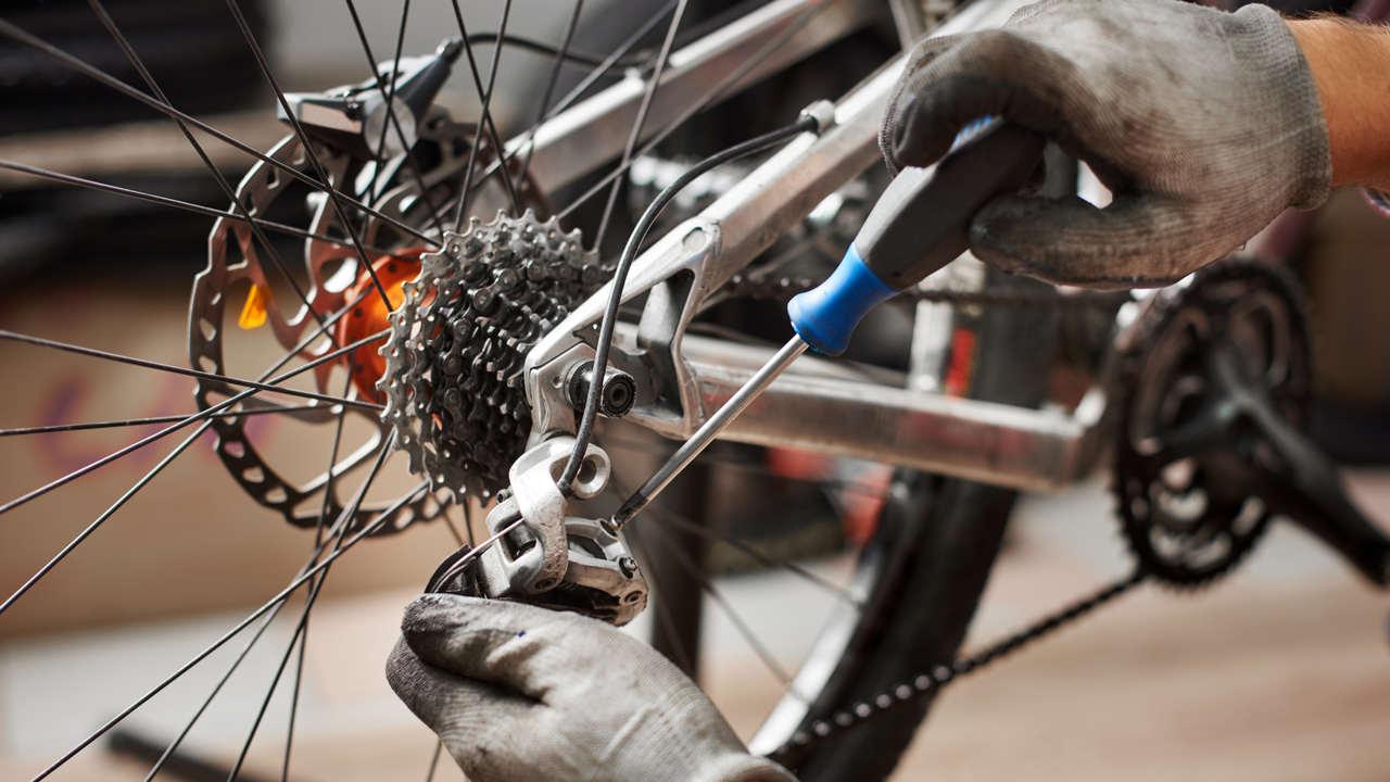 Mãos de mecânico regulando marcha de bicicleta