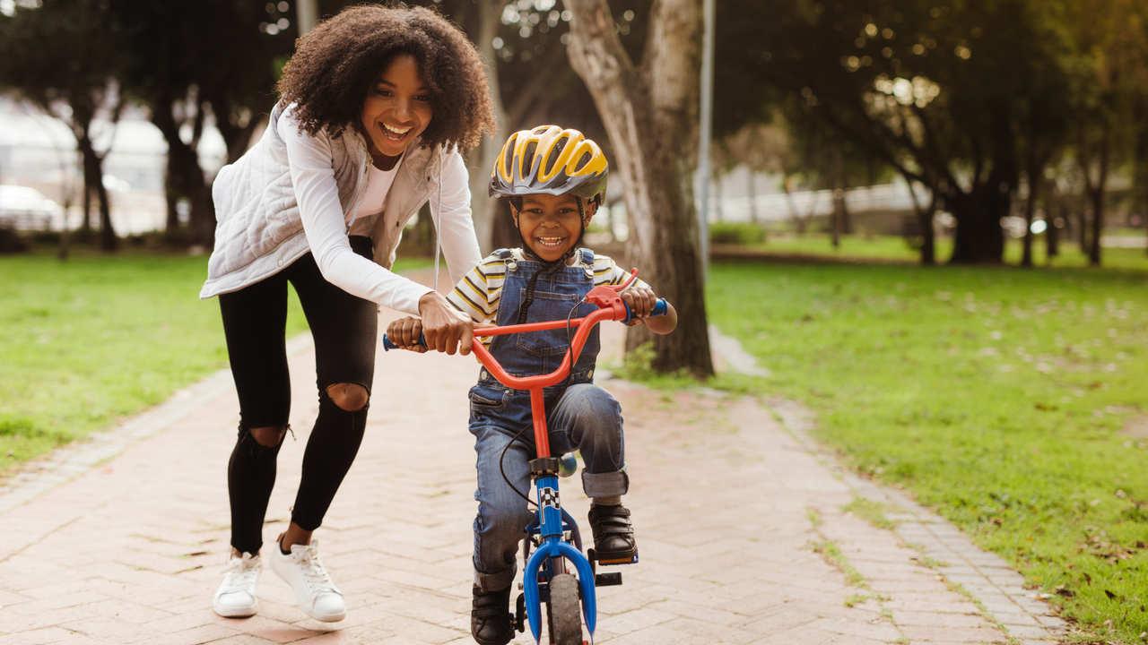 Mãe ajuda filho de capacete amarelo a andar de bicicleta aro 16 sem rodinha