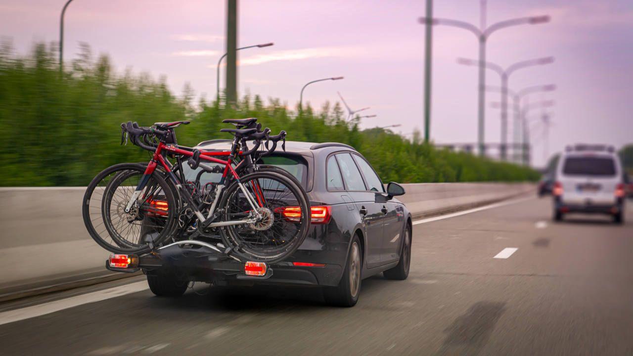Bicicletas encaixadas em carro em uma estrada