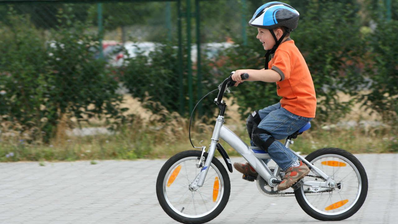 Menino caucasiano pedalando bicicleta ao ar livre