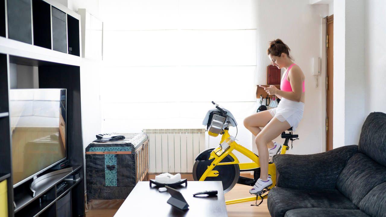 Mulher usa bicicleta ergométrica em casa