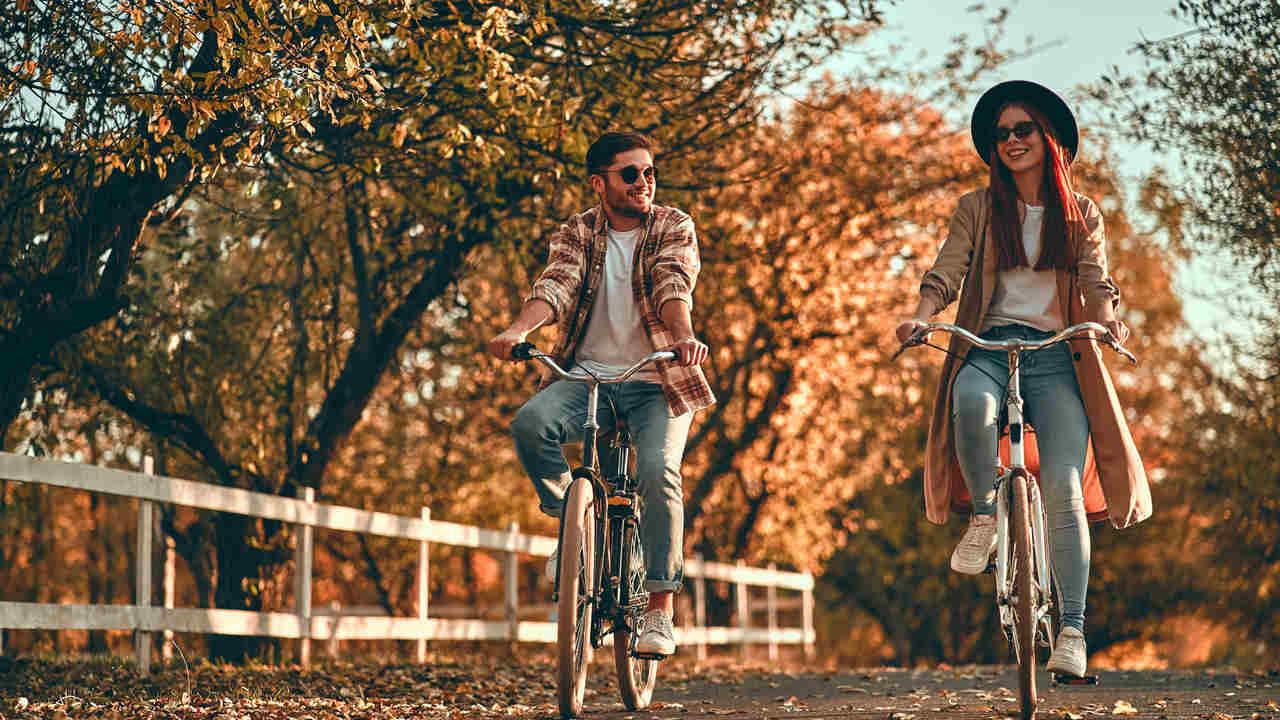 Homem e mulher jovens usando jeans, camiseta branca e blusa marrom, andando de bicicleta lado-a-lado em parque no outono