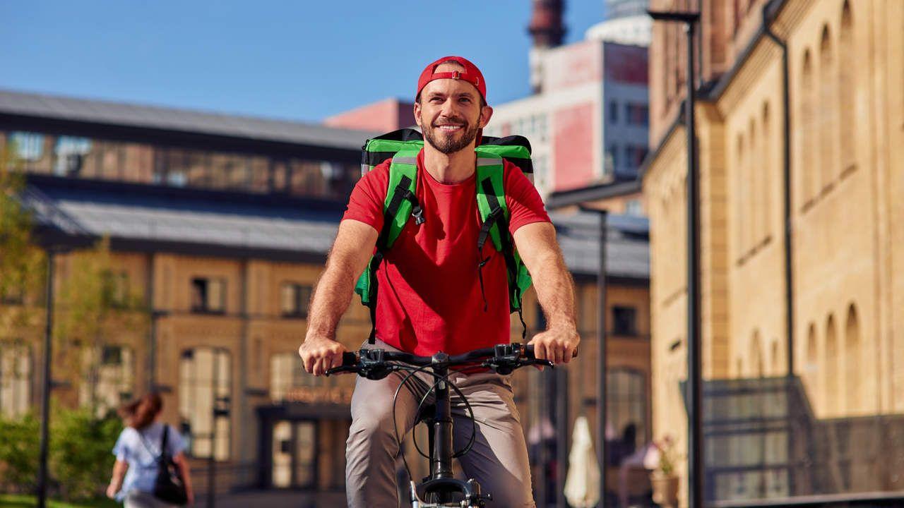 homem de barba sentado em bicicleta e sorrindo, vestindo camiseta e boné vermelho, calça marrom e bag de entregador delivery na cor verde limão