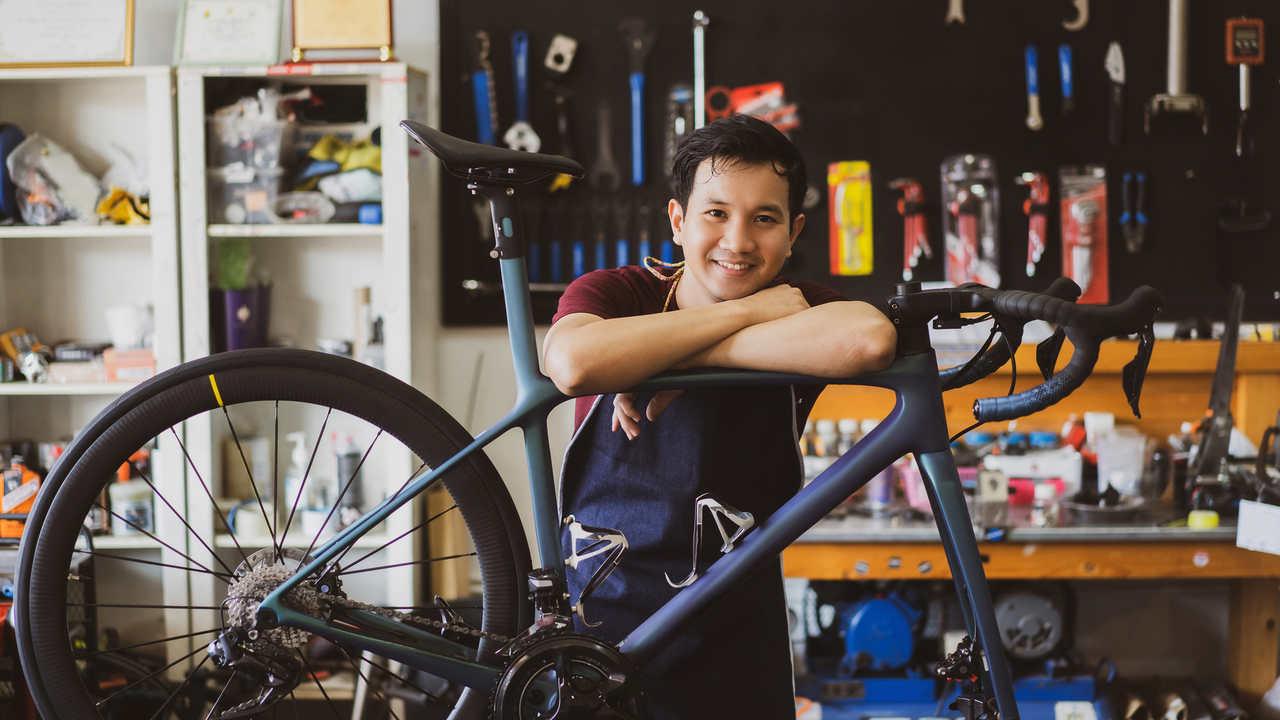 Mecânico apoiado em bicicleta sem a roda da frente em oficina