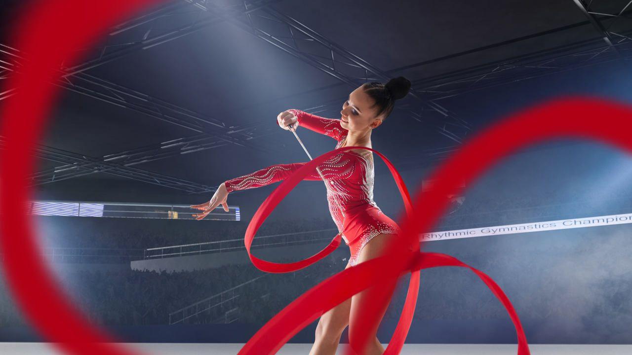 Ginasta caucasiana fazendo movimento com fita vermelha