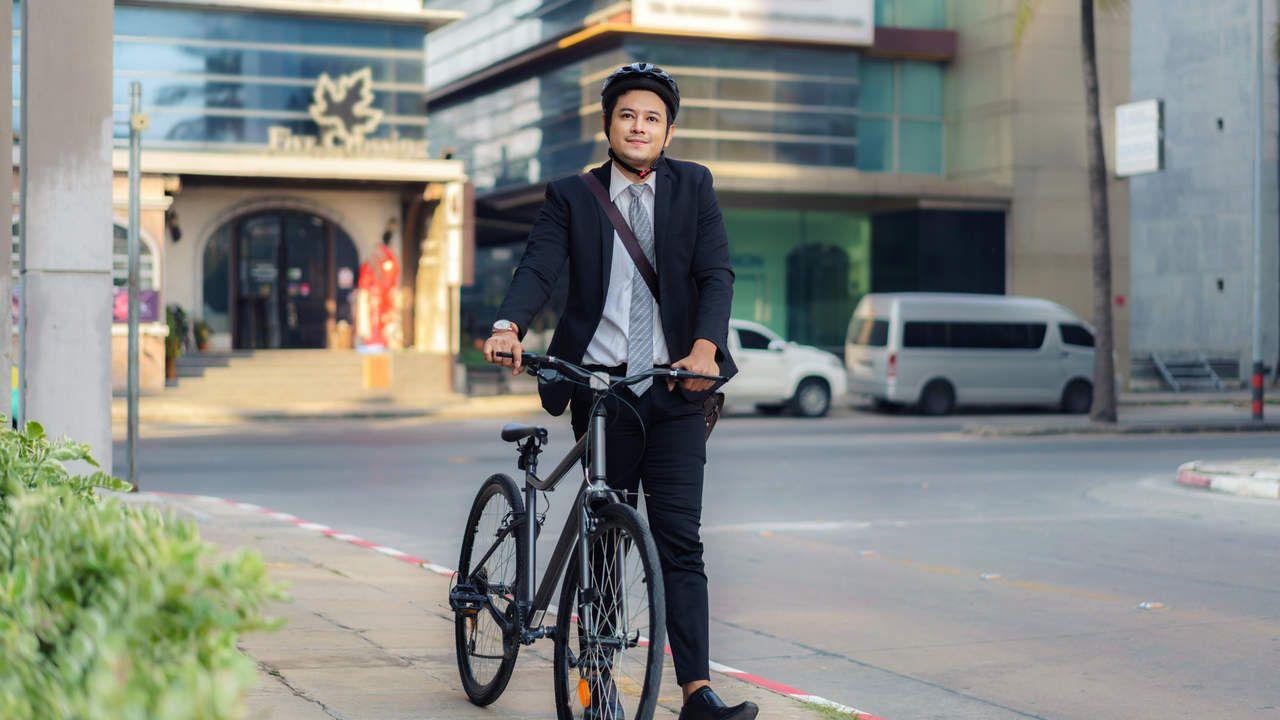 Homem asiático usando terno e capacete para ciclismo, carregando sua bicicleta lateralmente na calçada de um centro urbano, preparando-se para ir ao trabalho de manhã