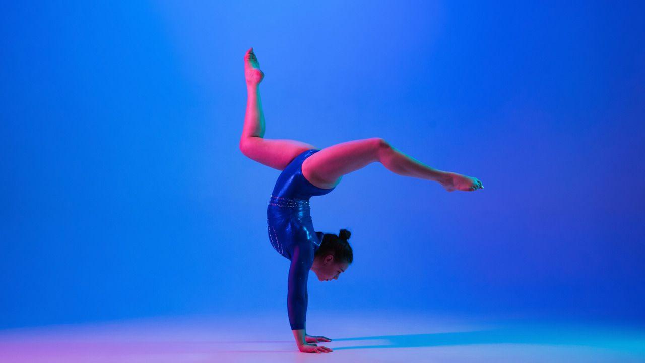 Ginasta caucasiana exercendo movimento em fundo azul com luz rocha