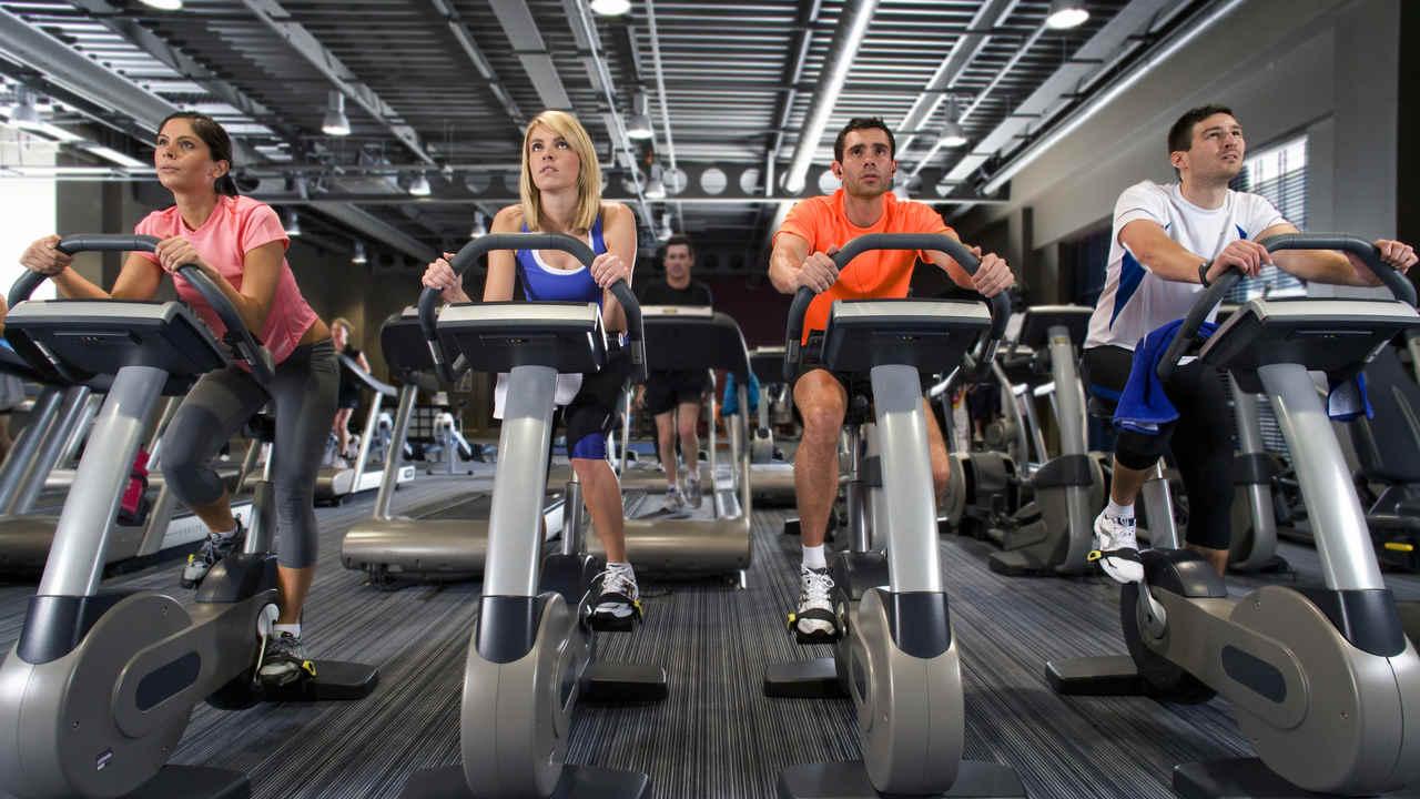Bicicletas ergométricas sendo usadas por pessoas em uma academia