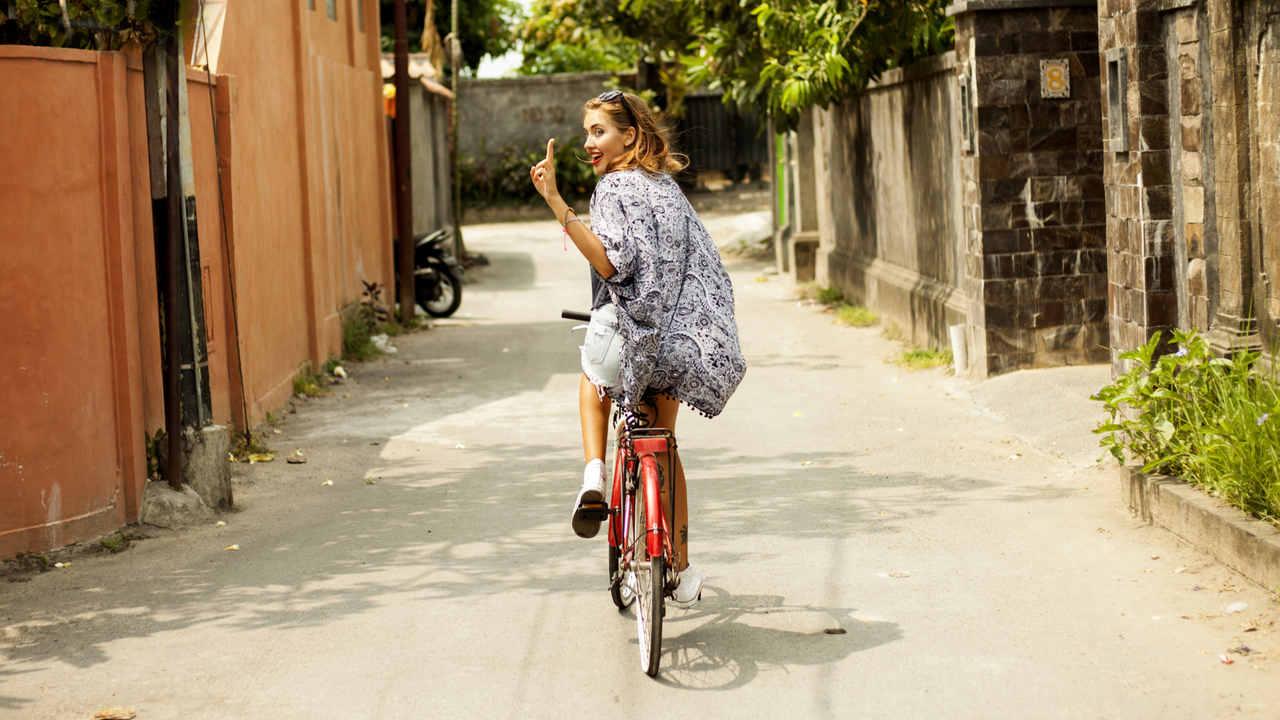 """Mulher jovem e loira usando roupa estilo hippie e andando em bicicleta vermelha em rua residencial. Está de costas para a câmera e fazendo sinal de """"paz e amor com os dedos', mostrando a língua"""