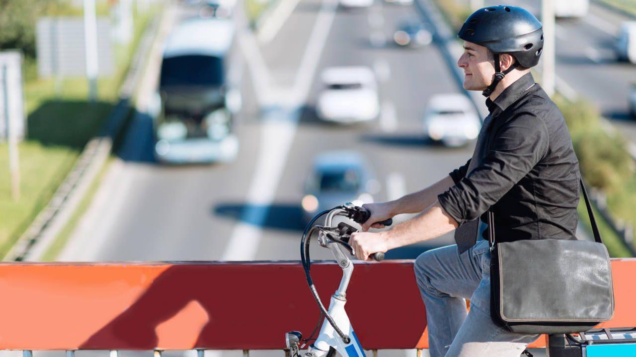 Homem atravessando viaduto com bicicleta motorizada branca e azul, usando capacete, camisa preta e calça jeans
