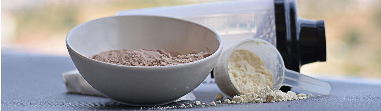 suplementos proteicos na frente de coqueteleira vazia
