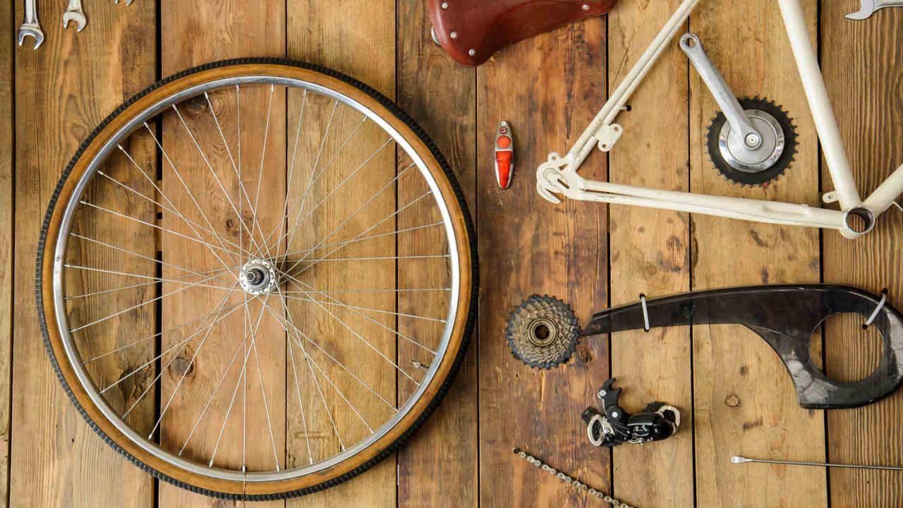 Peças de bicicleta desmontada em cima de mesa de madeira