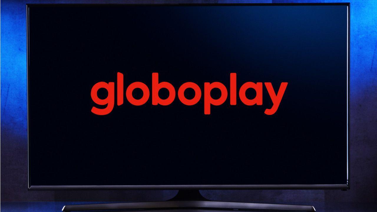Close de uma TV plana ligada no o logo da Globoplay. O fundo da foto é azul
