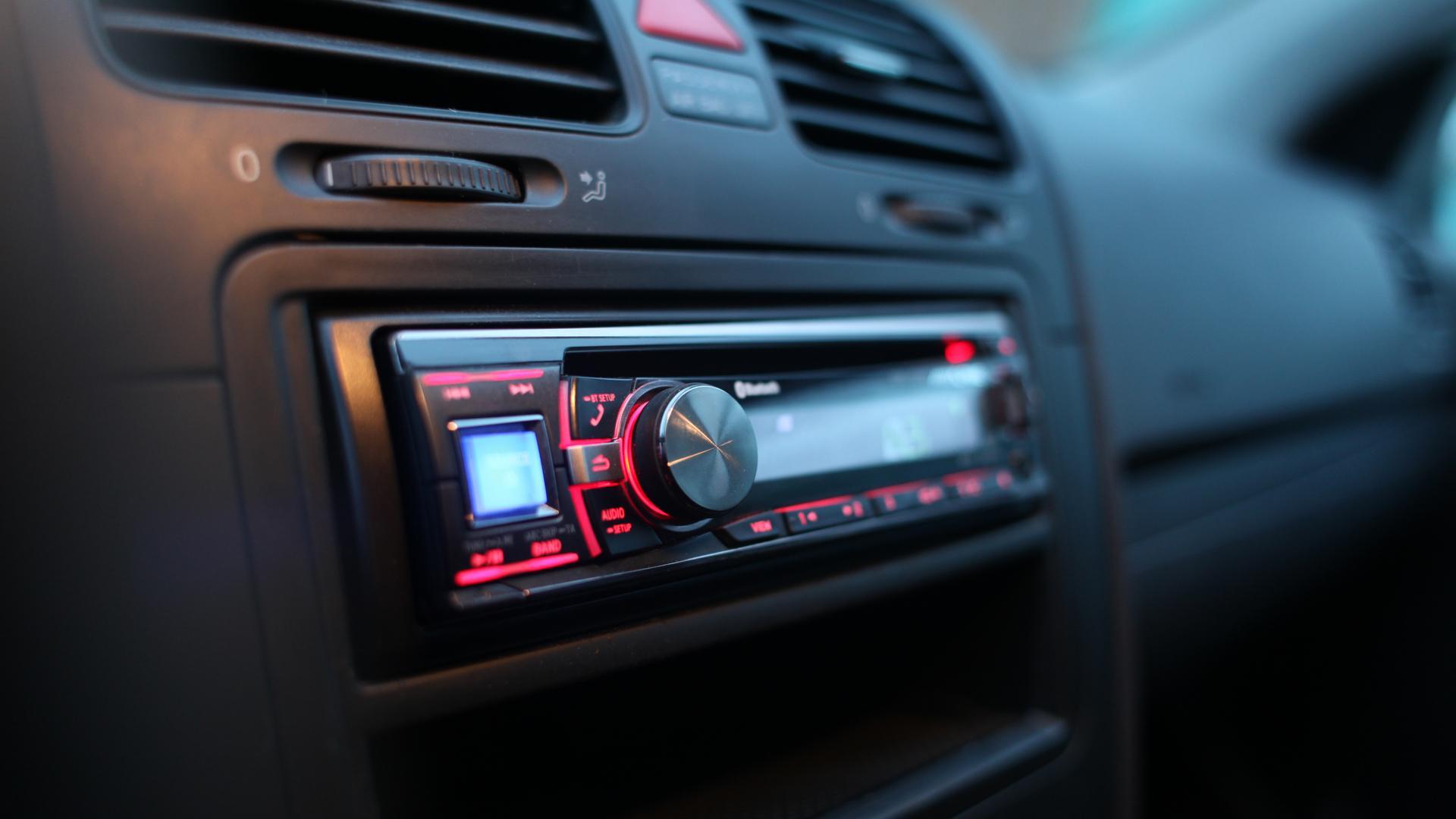 Som automotivo com detalhes de luzes e botões em vermelho