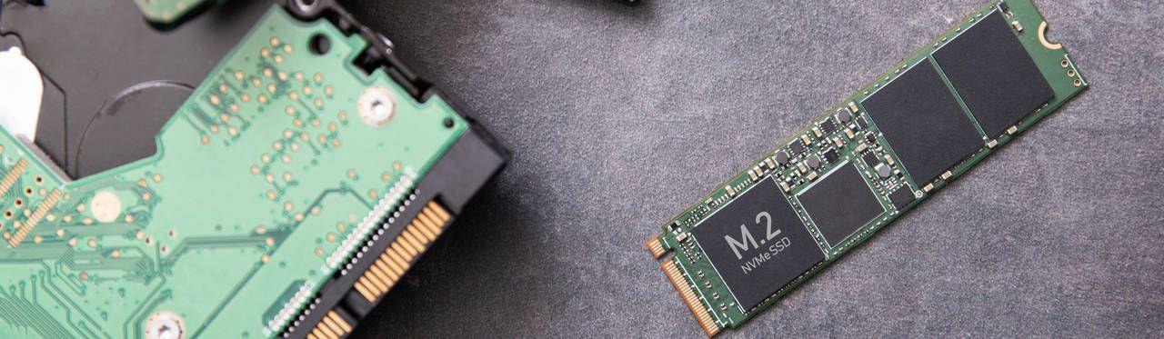 Um pequeno SSD M.2 à esquerda em comparação com um HD antigo e grande à direita