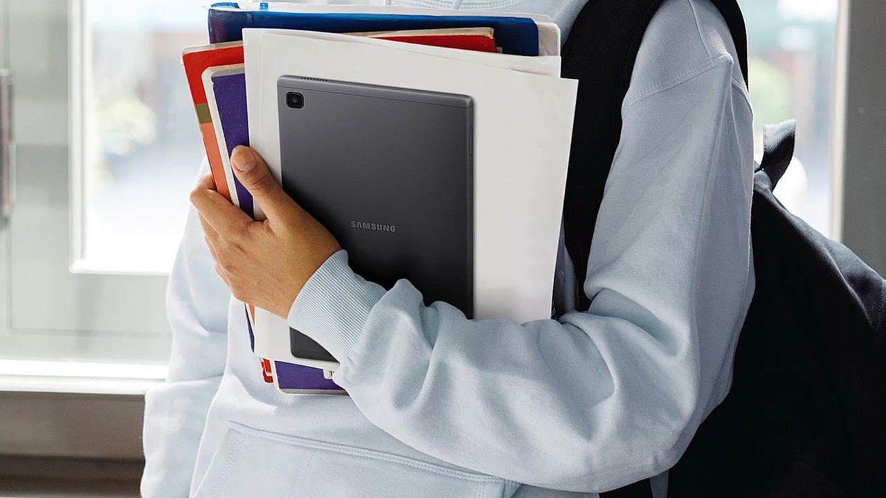 Pessoa segurando o Galaxy Tab A7 Lite junto a alguns livros