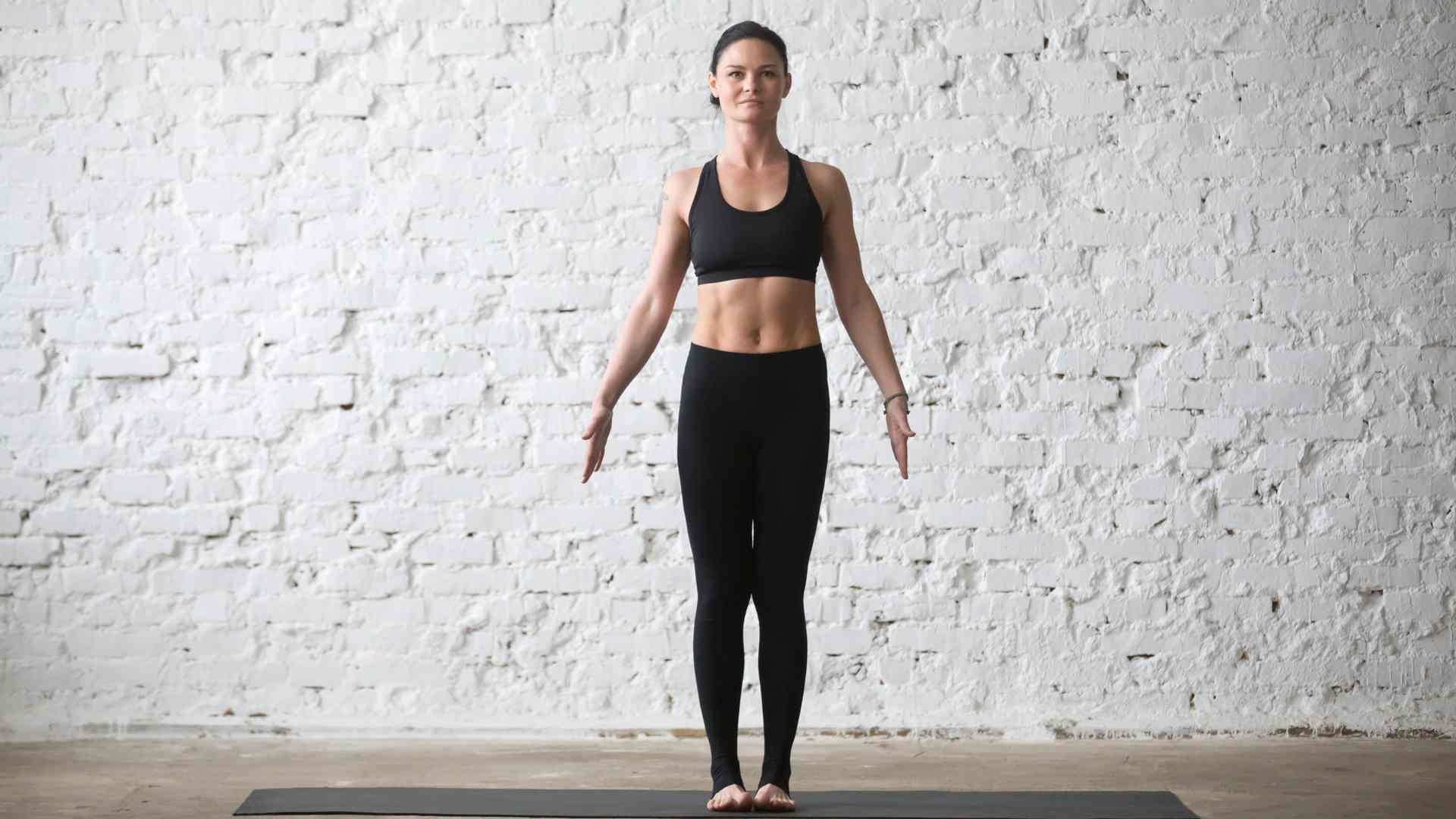 Mulher fazendo postura de yoga em pé