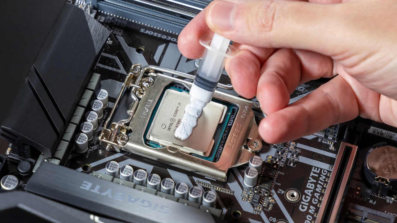 Técnico de informática aplicando pasta térmica sob processador instalado em placa-mãe