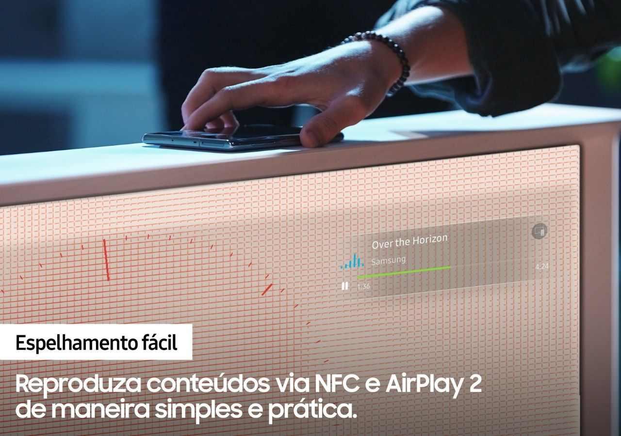 Mão encostando um celular no topo da The Serif para conectá-lo à TV.