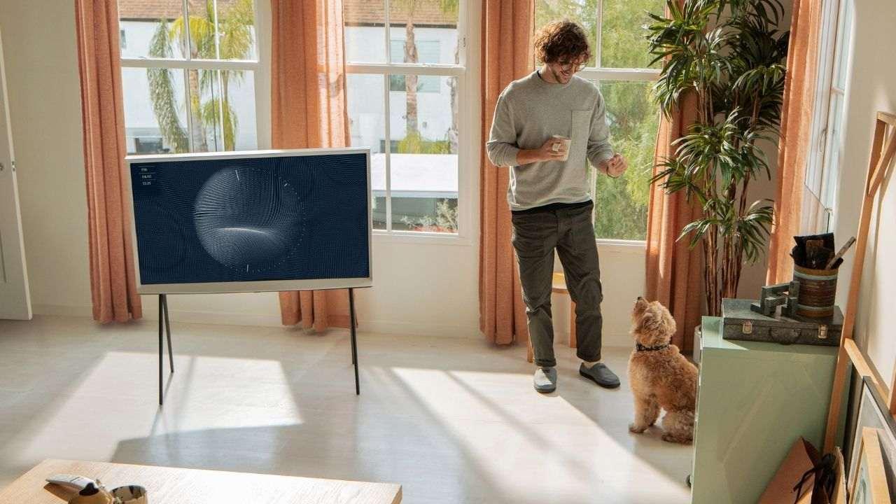 Sala de estar com a smart TV Samsung The Serif sobre o suporte para chão.