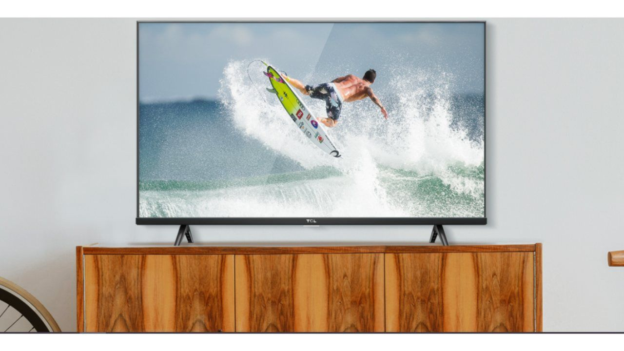 TV TCL S615 apoiada em rack de madeira clara com com tela mostrando um homem surfando