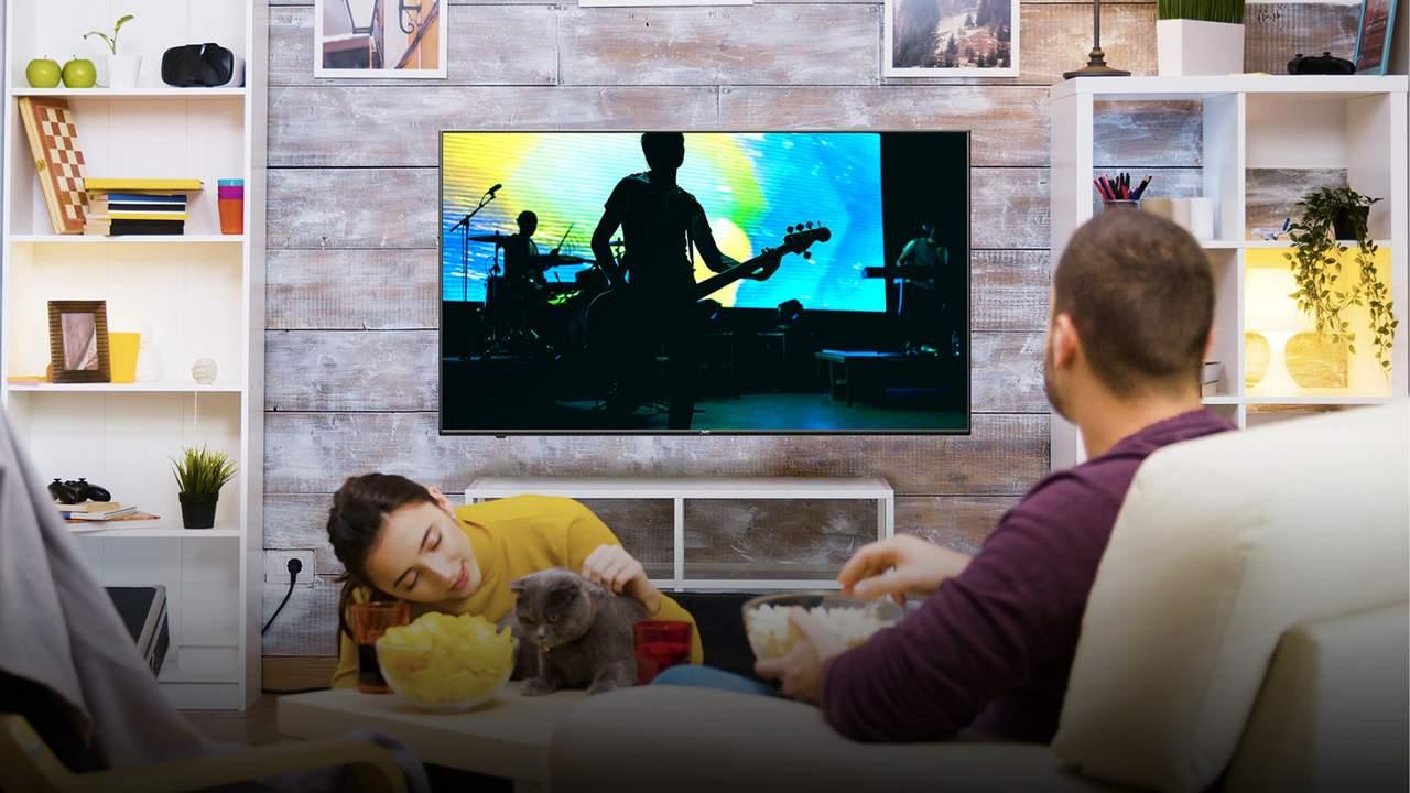 Homem comendo pipoca e assistindo show na TV JVC e mulher acariciando o gato de estimação