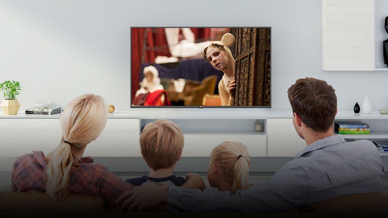 Família sentada no sofá da sala de estar assistindo uma TV da JVC