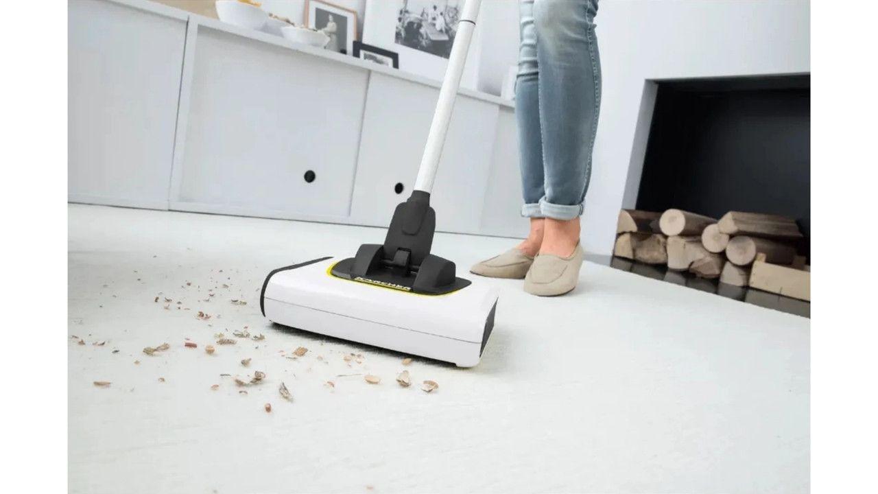 Vassoura elétrica da Karcher aspirando partículas sólidas no chão branco