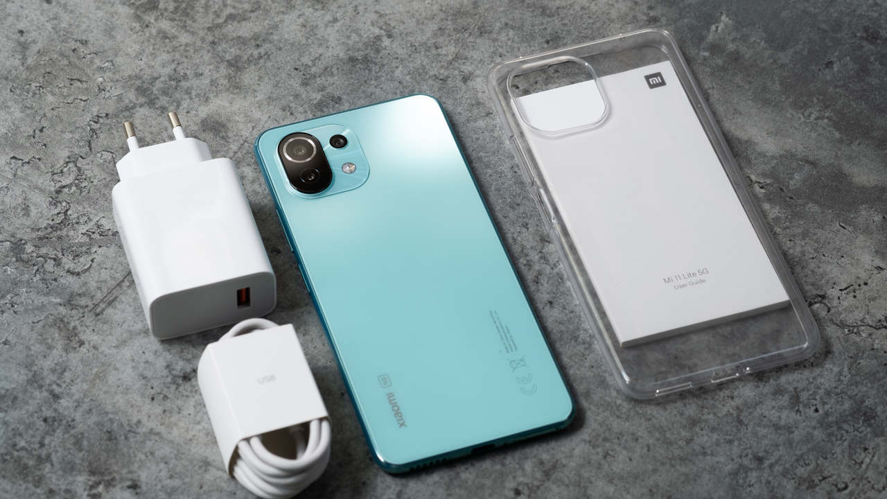 Celular Mi 11 Lite deitado com traseira para cima em superfície cinza com carregador do lado esquerdo e capinha transparente do lado direito