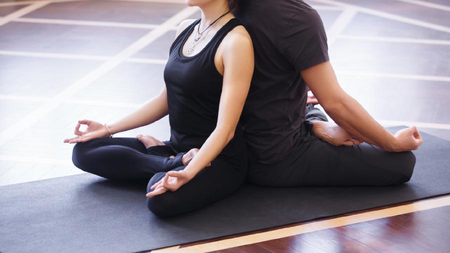 Entenda os benefícios e como fazer yoga em dupla! (Imagem: Reprodução/Shutterstock)