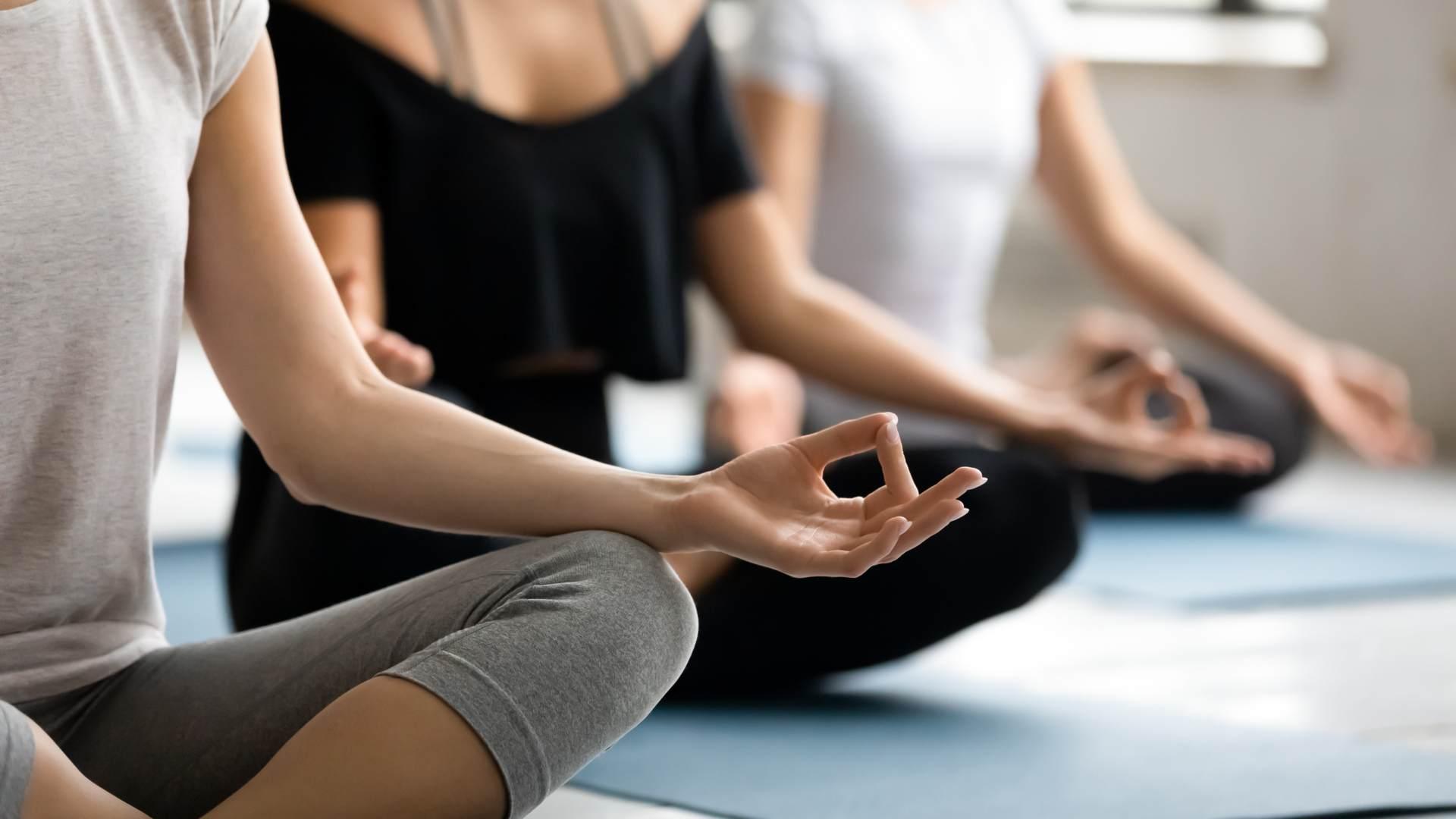 Mulheres fazendo gestos com as mãos na aula de yoga